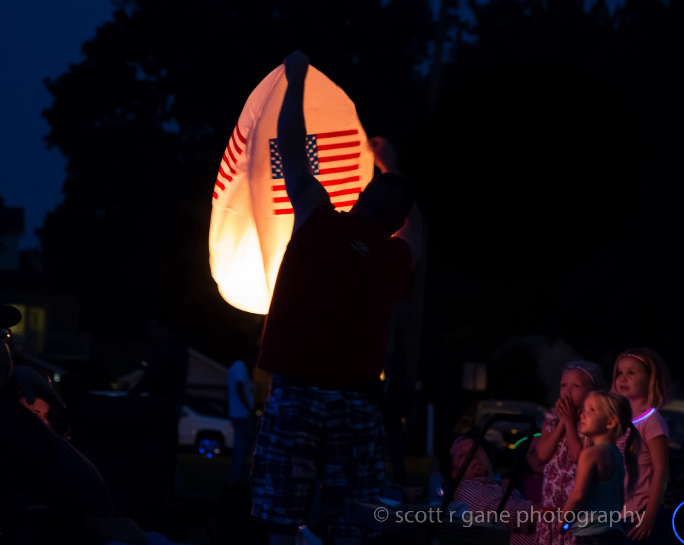 Independence: Dad lighting lantern for daughters looking on.