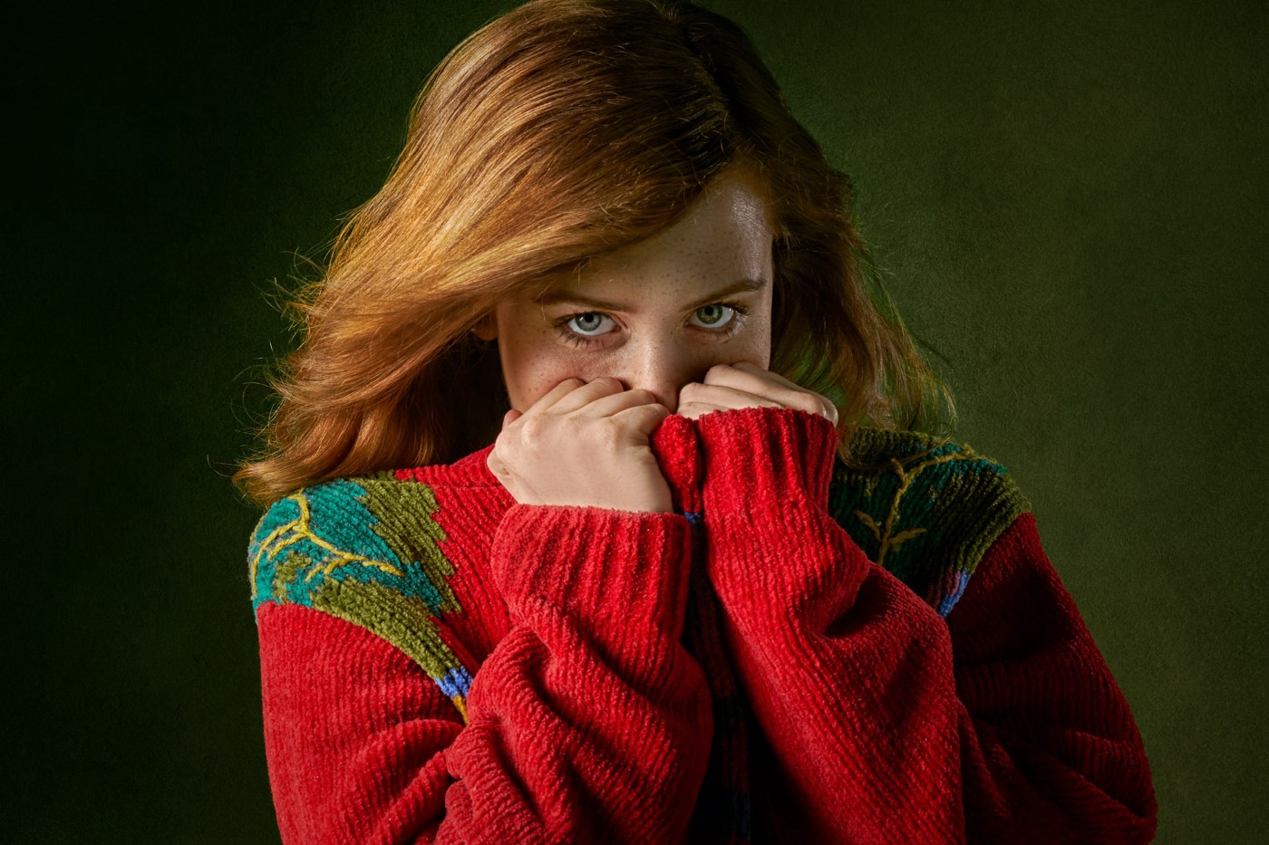 A red haired woman hiding the bottom half of her face with a sweater.
