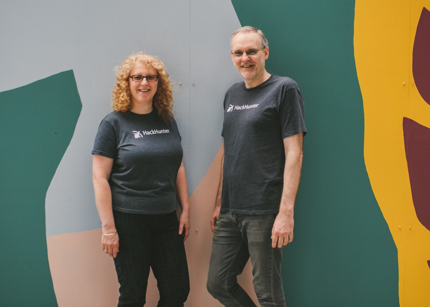 HackHunter Co-Founders Tracie Thompson and Mike Thompson pose in front of a colourful wall.