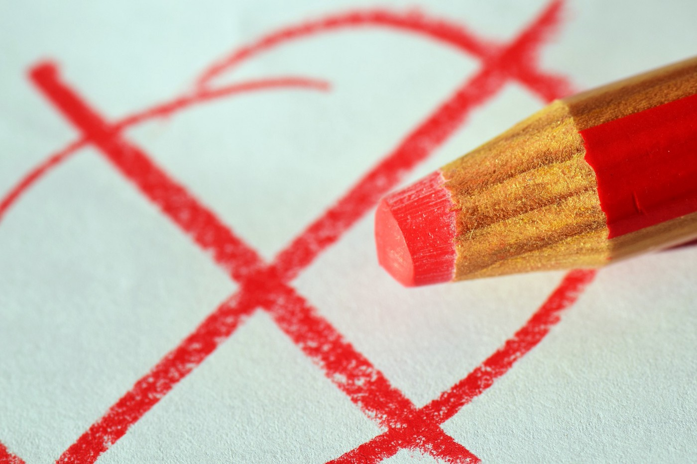 "A worn down red pencil over top a scribbled ""x"" mark"