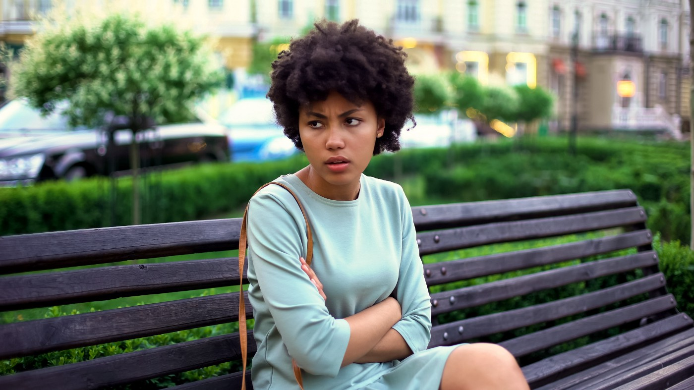 A photo of an annoyed black woman sitting on a park bench.