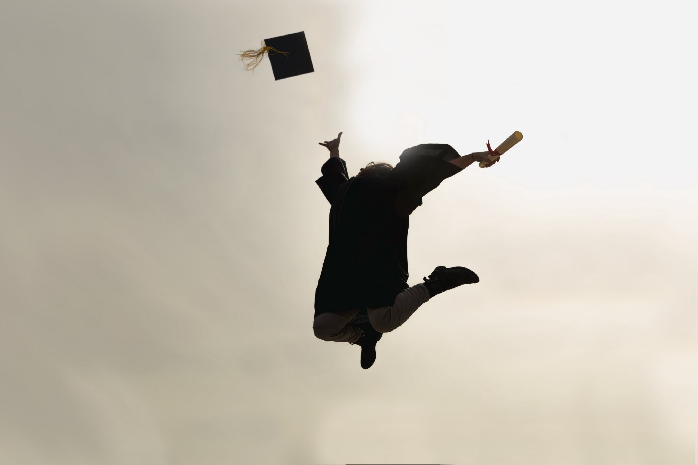 Person wearing graduation gown jumping in the air and throwing their cap