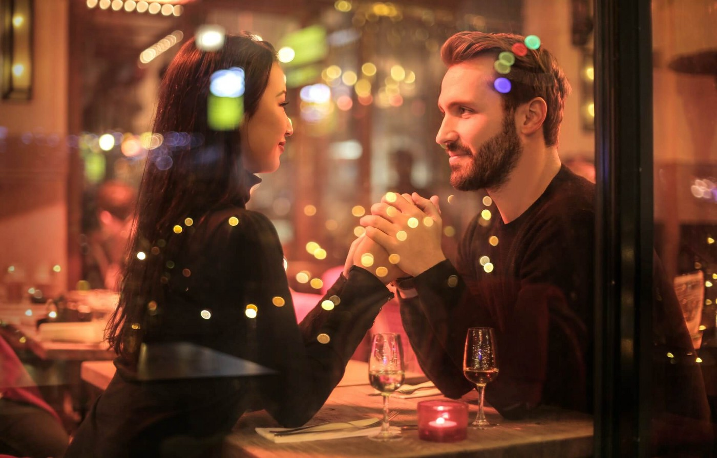 Couple holding hands over a dinner table while looking in each other's eyes depicting how true love happens at first sight.