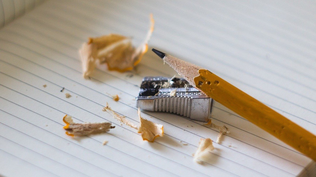 Pencil sharpener, pencil, and wood shavings on a notebook page.