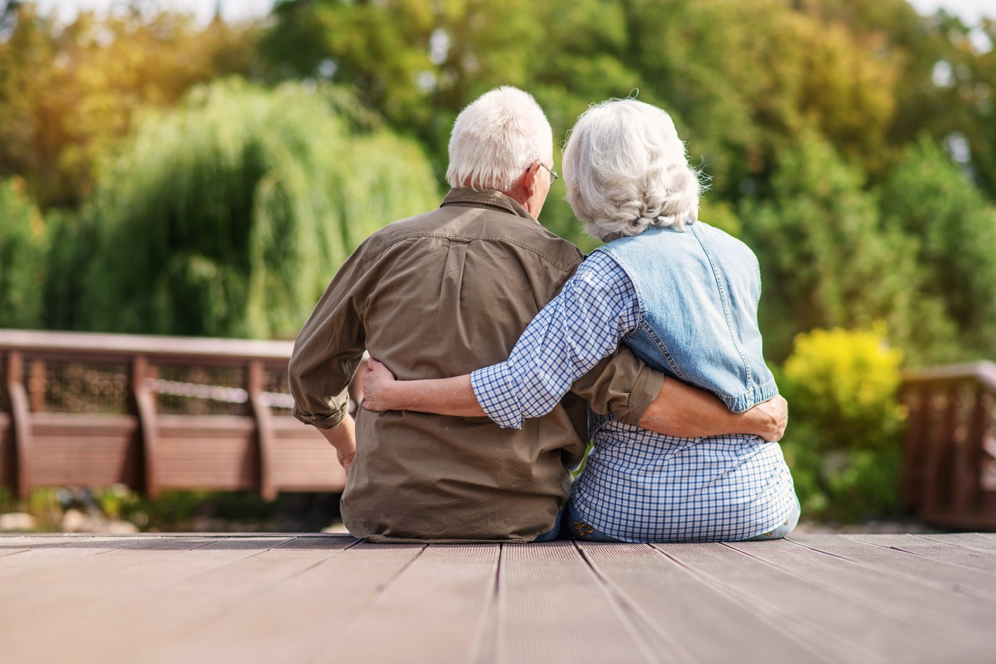 Back view of an old white man and woman holding each other outside a lakeside cabin with depth of field against the trees