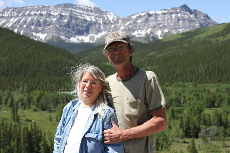 a loving married couple standing with the Rocky Mountains behind them on a sunny summer day