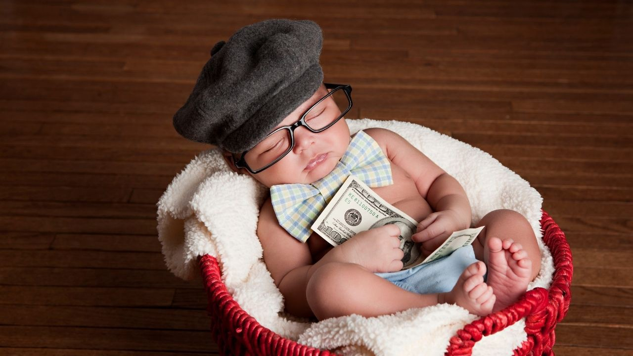 Baby is dressed like a grown up with a bow tie, hat and glasses and is sleeeping while he holds money as in a passive income