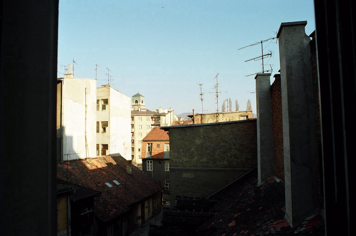 early 90s view of the courtyard from the apartment i grew up in, the green top of a church tower can be seen in the distance, many TV antennas against a pale blue sky on a sunny day.
