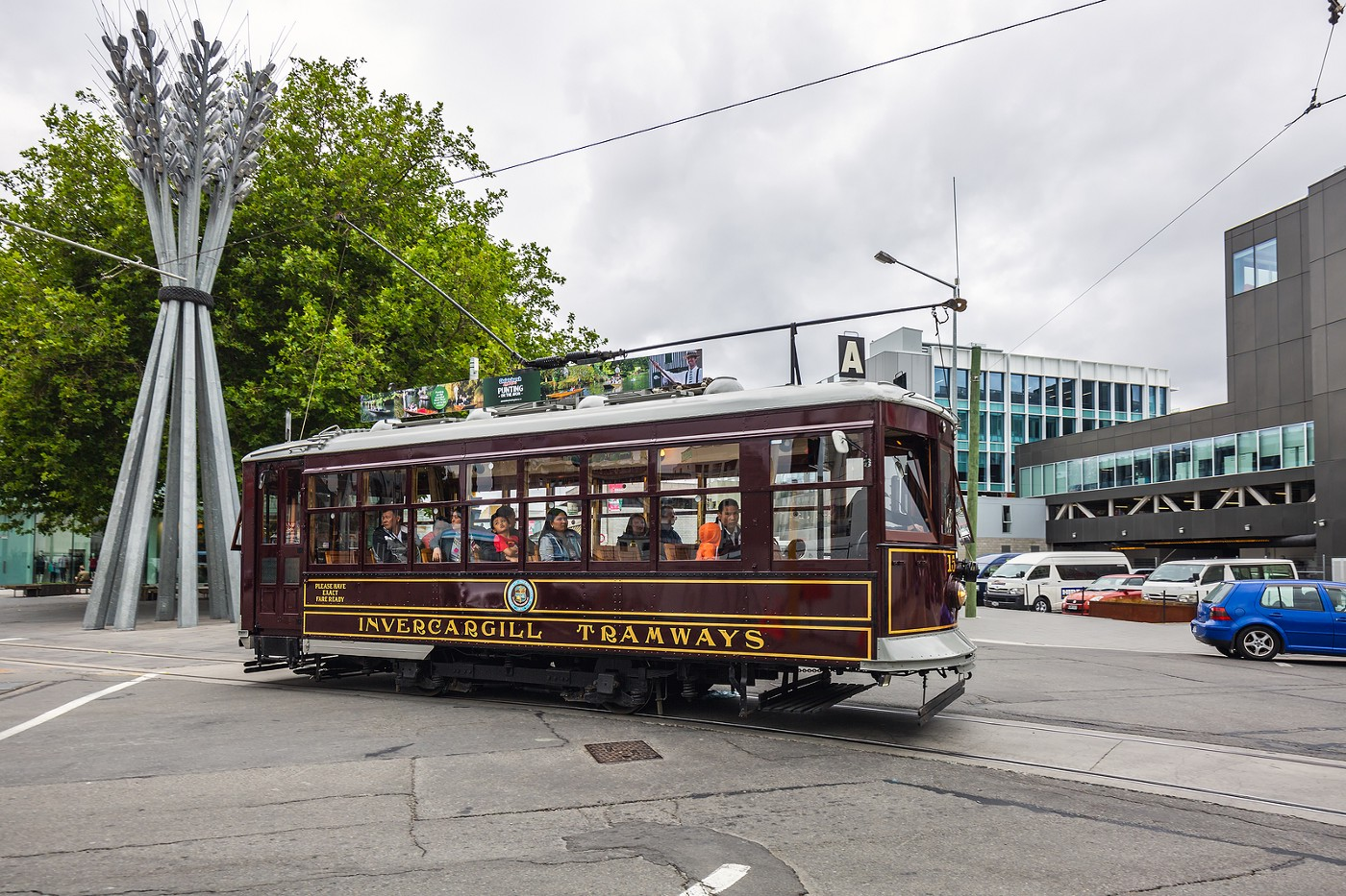 Old Invercargill Tramway tram at intersection. Coloured brown with yellow trim and modern city buildings in the background.