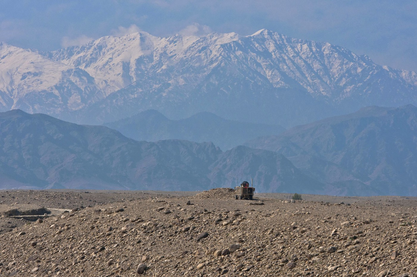 The mountains of Tora Bora loom over a lone U.S. mine resistant ambush protected vehicle as it patrols outside the Achin District Center, Nov. 5, 2011.