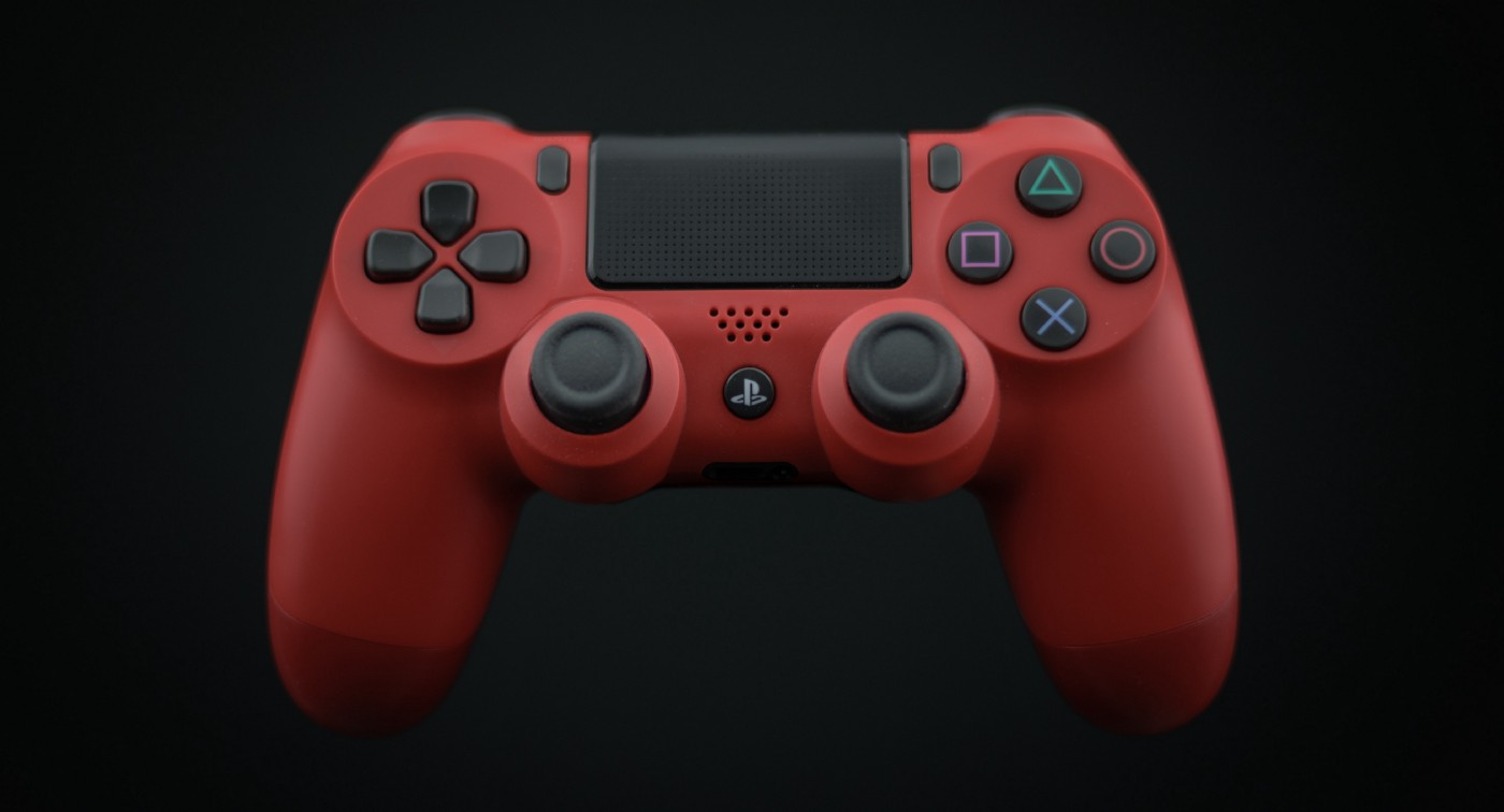 A red play station game controller against a black background