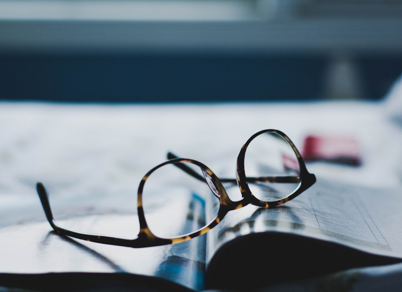 pair of dark-framed eyeglasses placed upside down on a magazine or book.