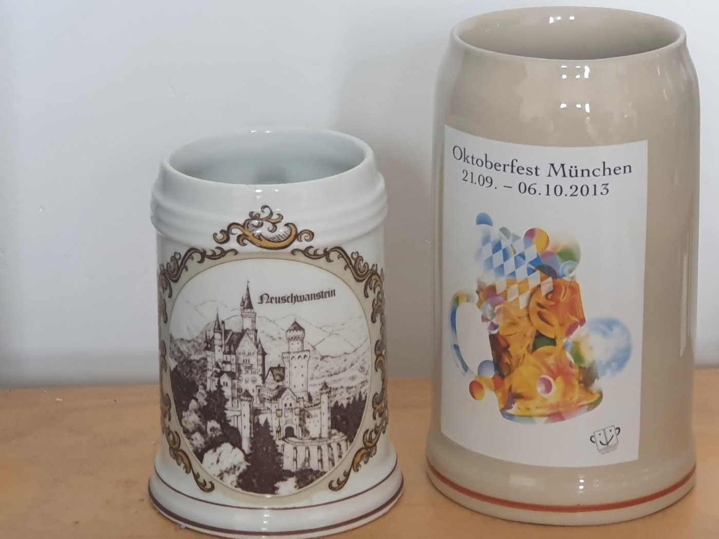 Two pewter beer steins side by side. One shows a picture of Neuschwanstein Castle and the other shows the logo for the Munich Beer Festival 2013