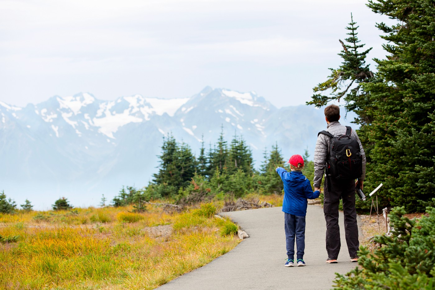 A boy points to snow-capped peaks in the distance.