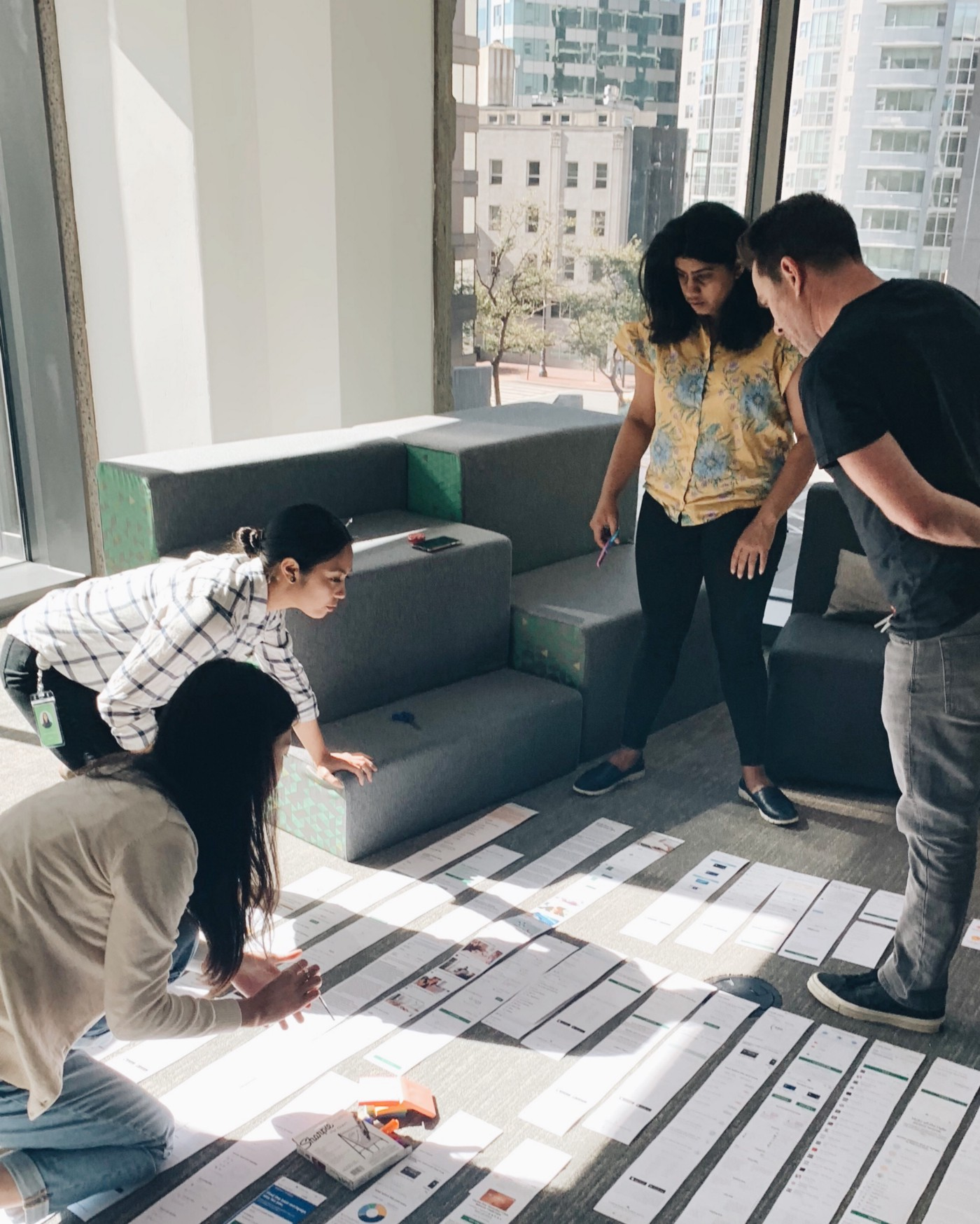 A photo of two people standing and two people kneeling. They're all looking at screenshots of a website that are printed out in long strips of paper and lined up on the ground.