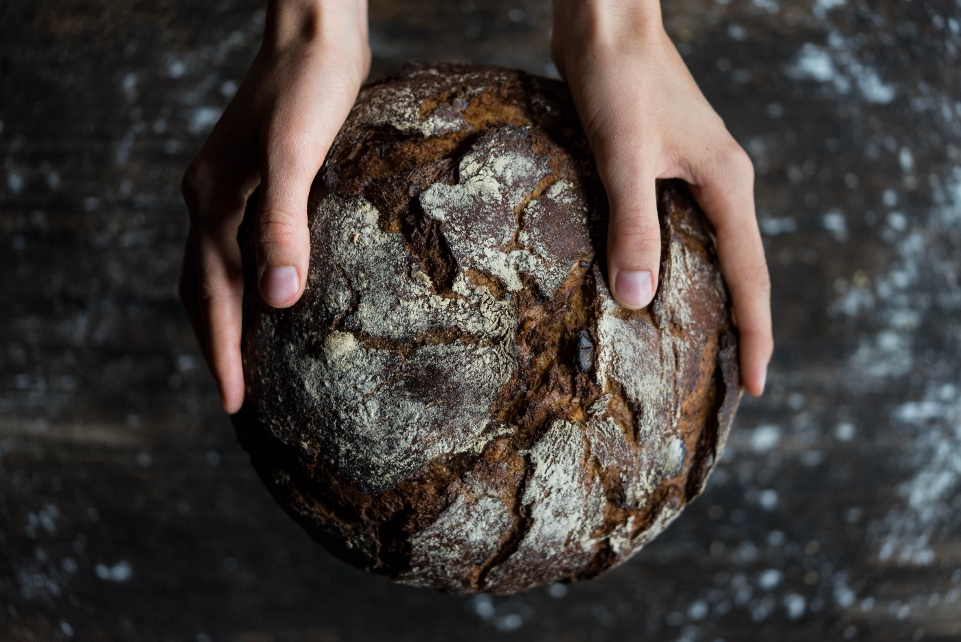 Hands hold a browned and crumpled ball resembeling the earth