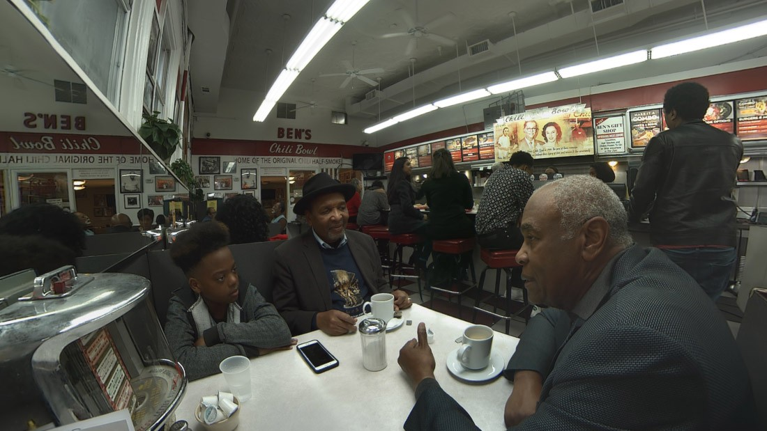 Two older black men and a young boy sit around a table, deep in conversation at Ben's Chilli Bowl in the USA.
