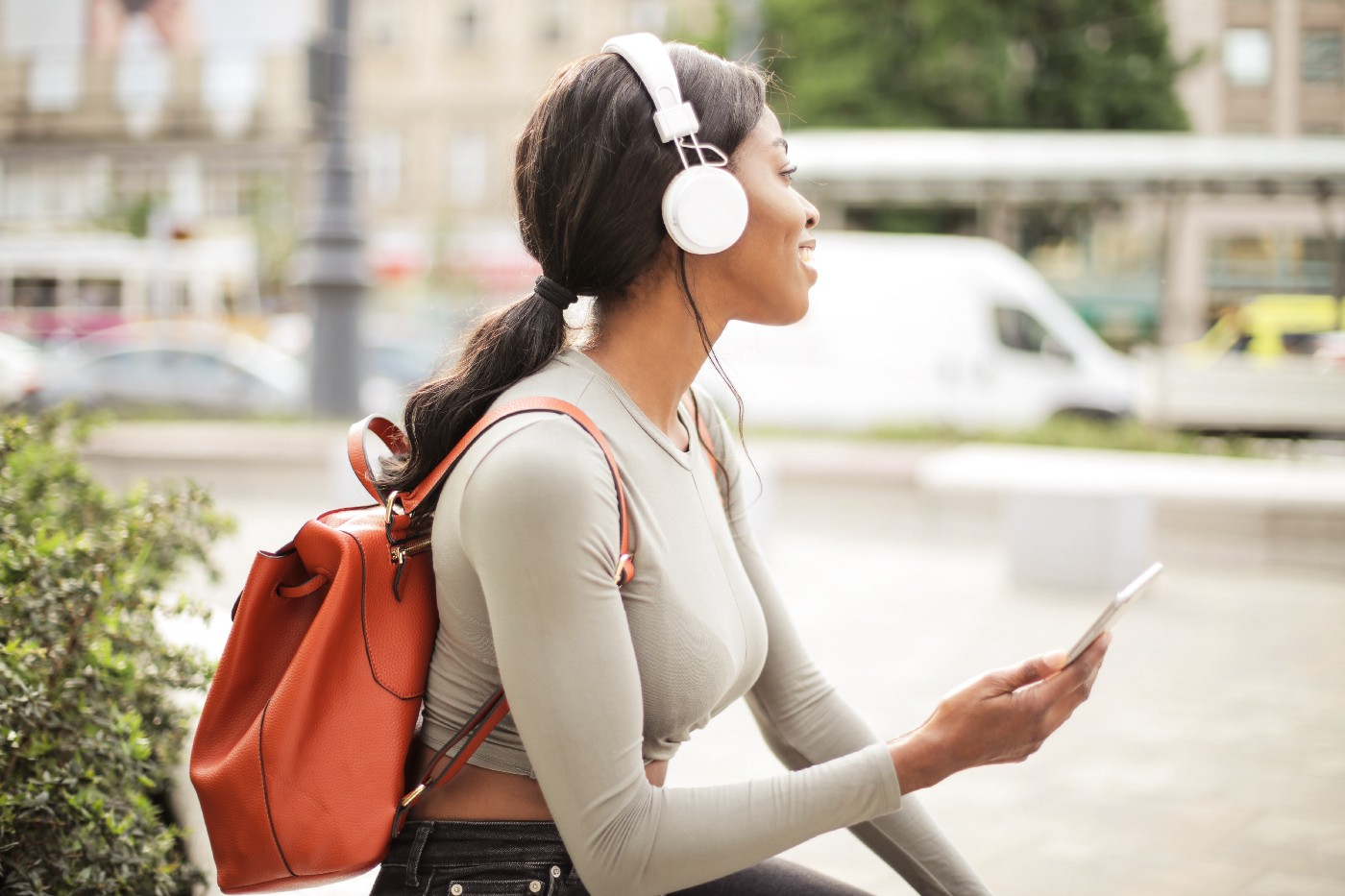 Woman with headphones on audio journaling with her phone while sitting down outside