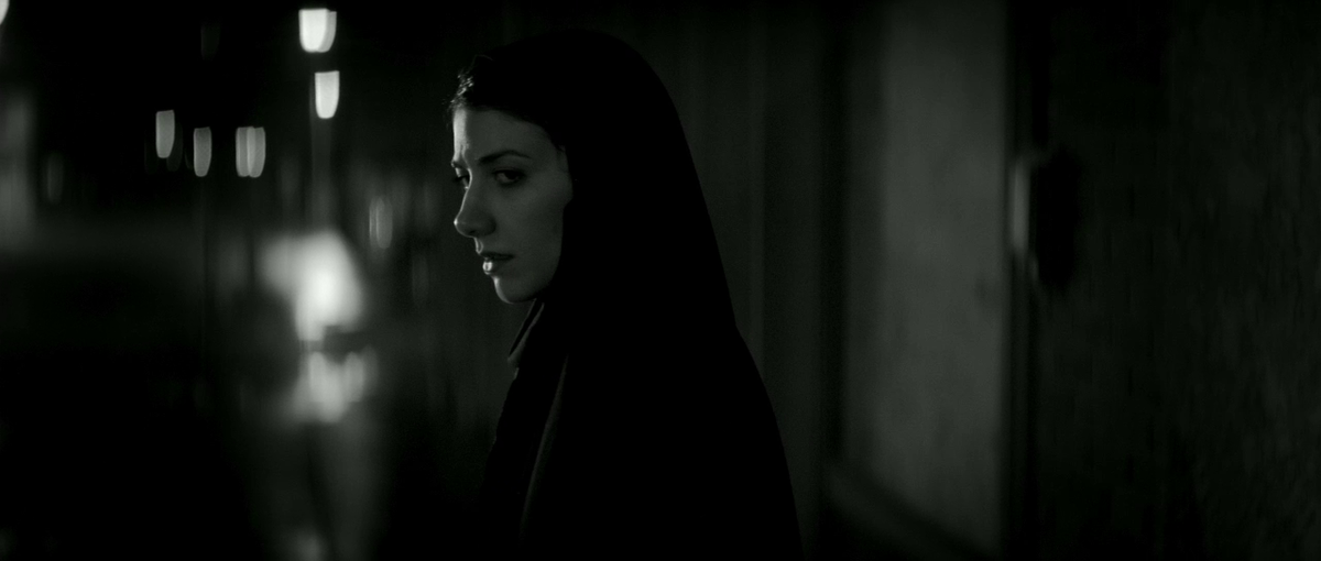 A female vampire in a chador begins to turn around to face the camera.