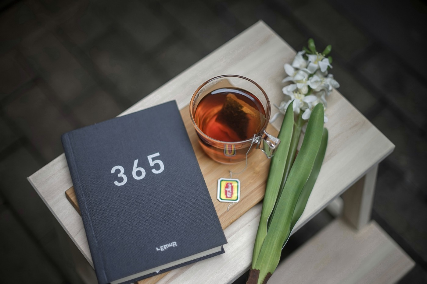 A black diary, a glass of tea, and a flower on a table.