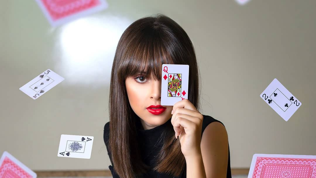 Lady holding up a playing card