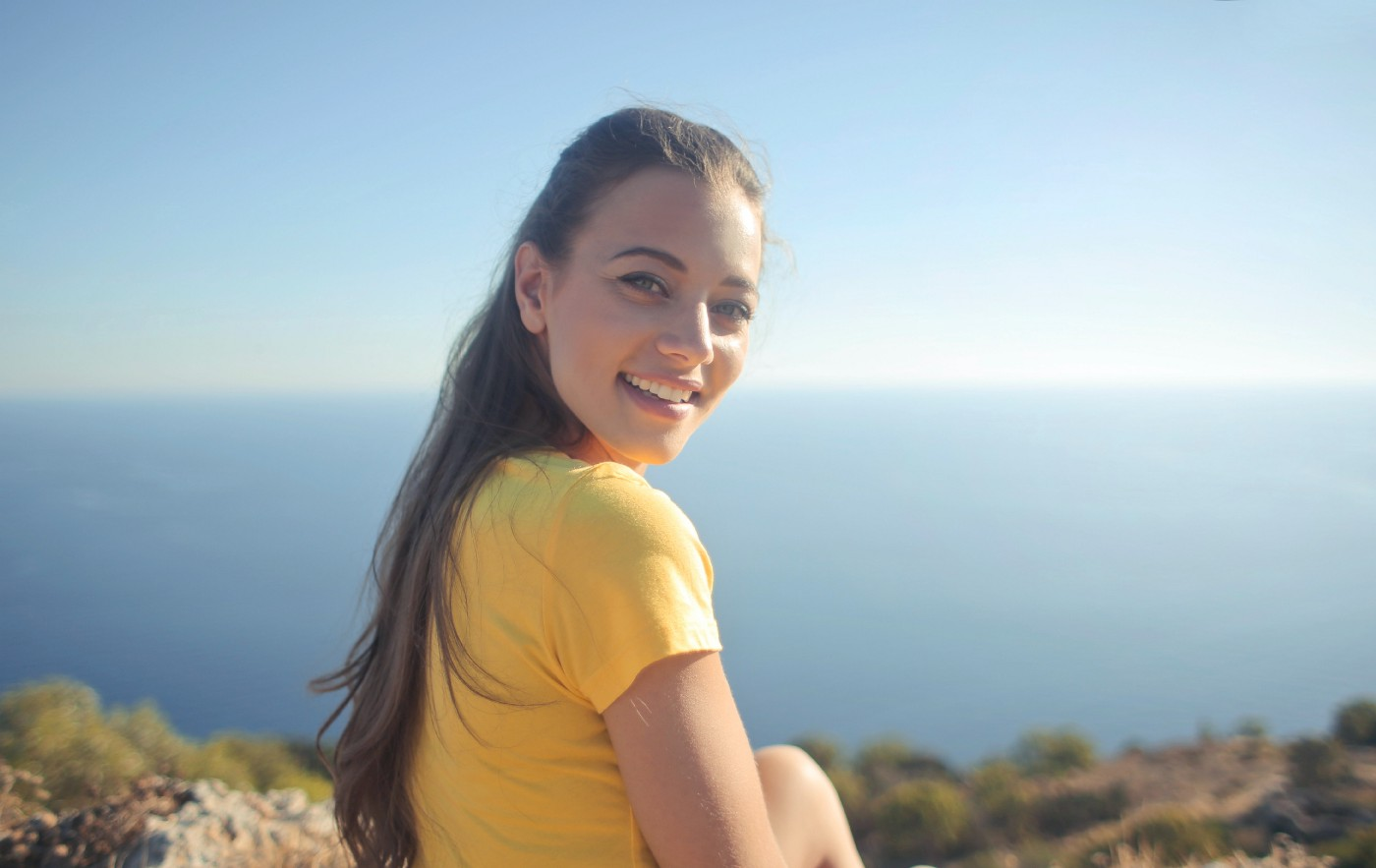 Woman smiling at the camera, wearing a yellow shirt. She is sitting on a mountain with a horizon behind her and ground below.
