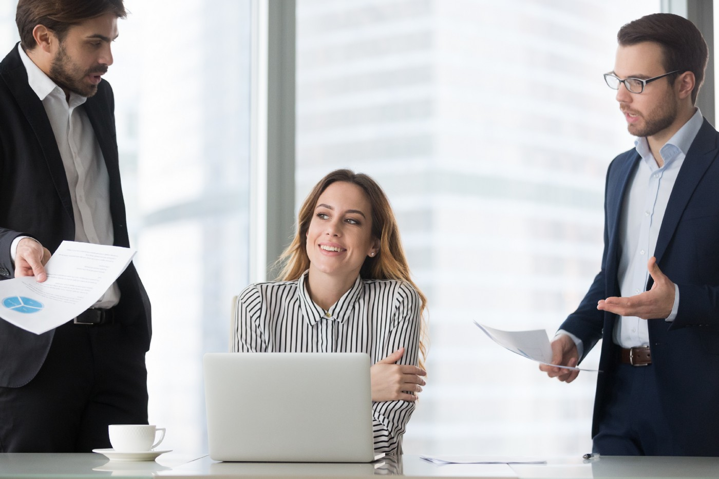 A businesswoman smiles awkwardly and looks away as two of her colleagues are bothering her with questions at her desk.