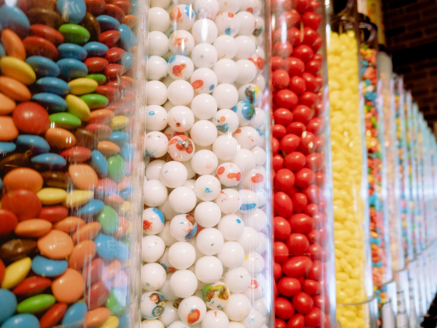 different types of candy sorted into glass jars