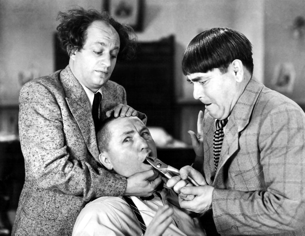 Black and white photo of the Three Stooges showing Curly Joe having his tooth pulled with a pair of pliers by Moe, while Larry holds Curley's head still.
