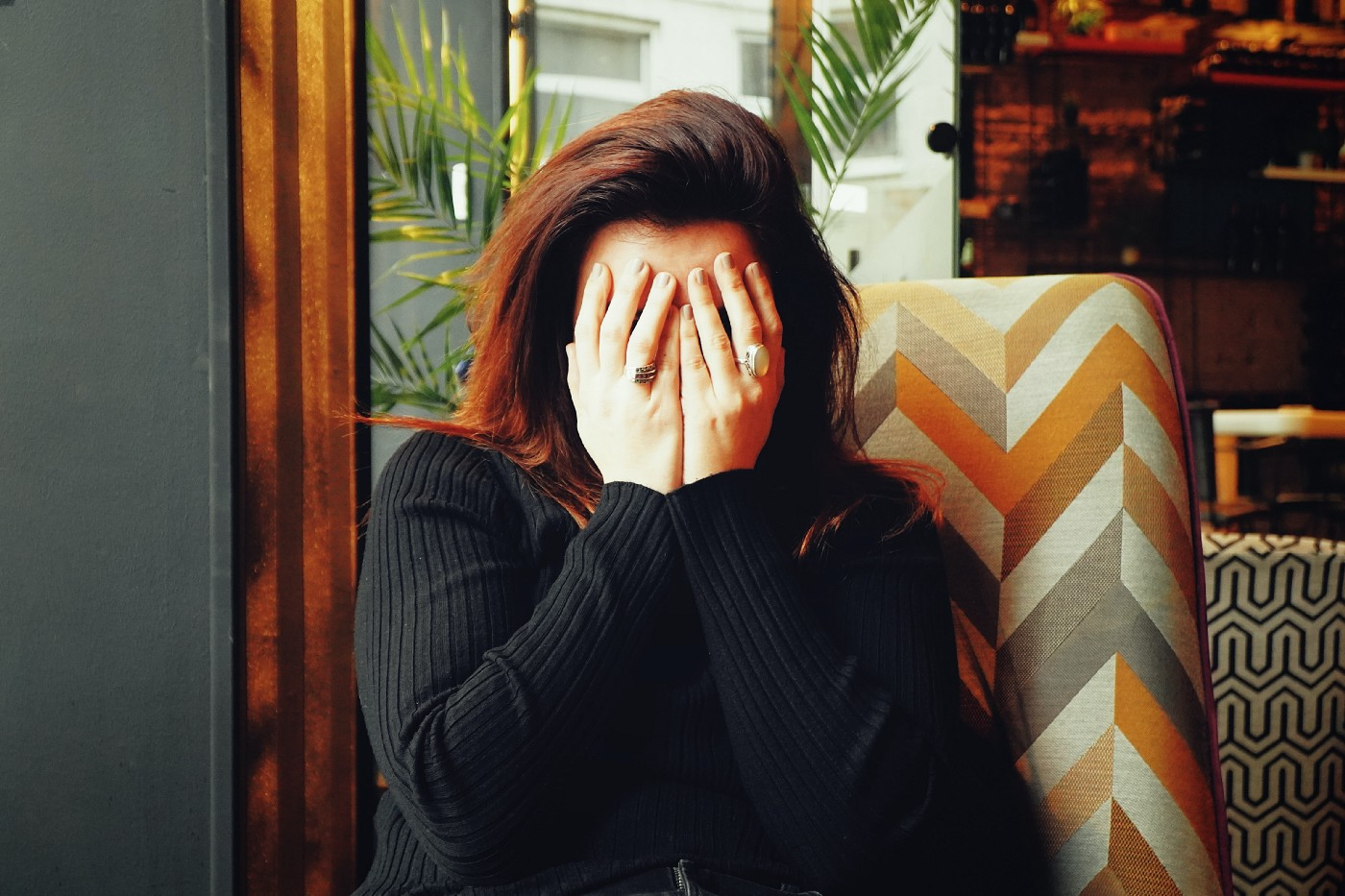 Woman in a black jumper covering her face.