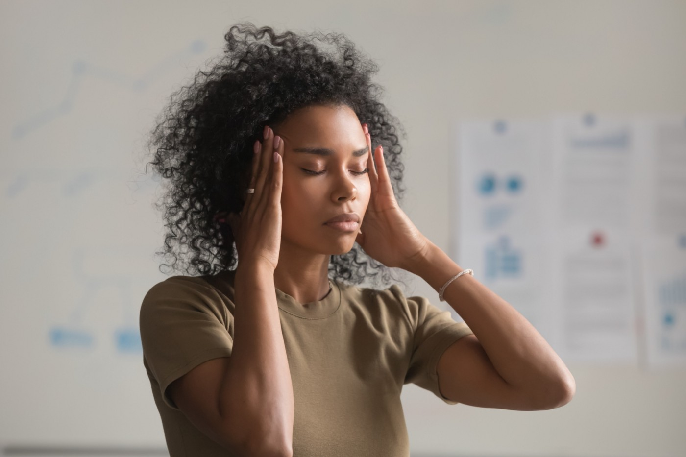 A photo of an exhausted black women with her hands on her temples.