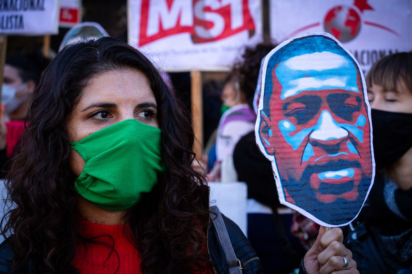 A woman wearing a face mask holds up a sign of George Floyd at a protest in Buenos Aires, Argentina.
