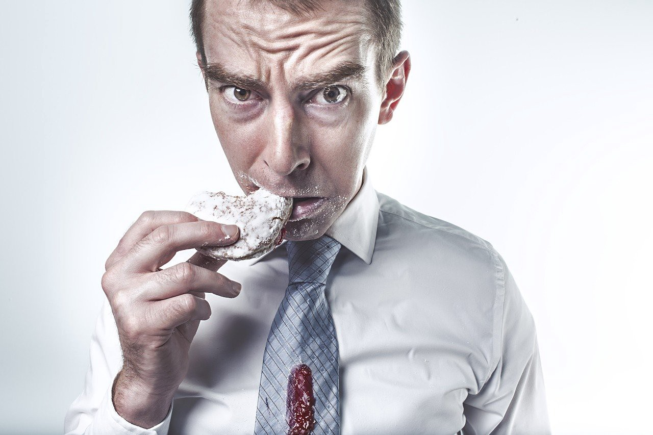 Middle aged white man eating a rice cake, wearing a suit. His blue tie is covered in a red sauce, possibly jam, and his face is covered in white dust around the mouth. He looks distressed and is staring straight at the reader.