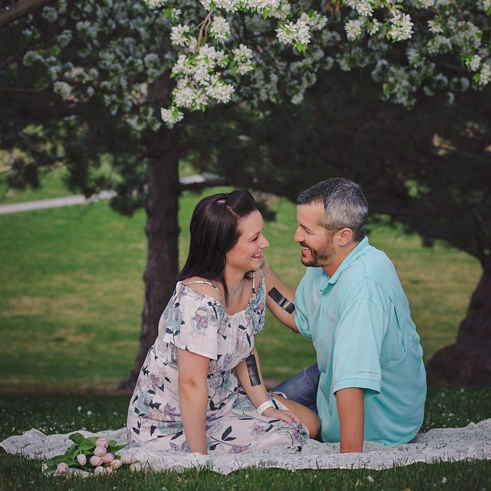 Shanann and Chris Watts sitting in a park smiling at each other.