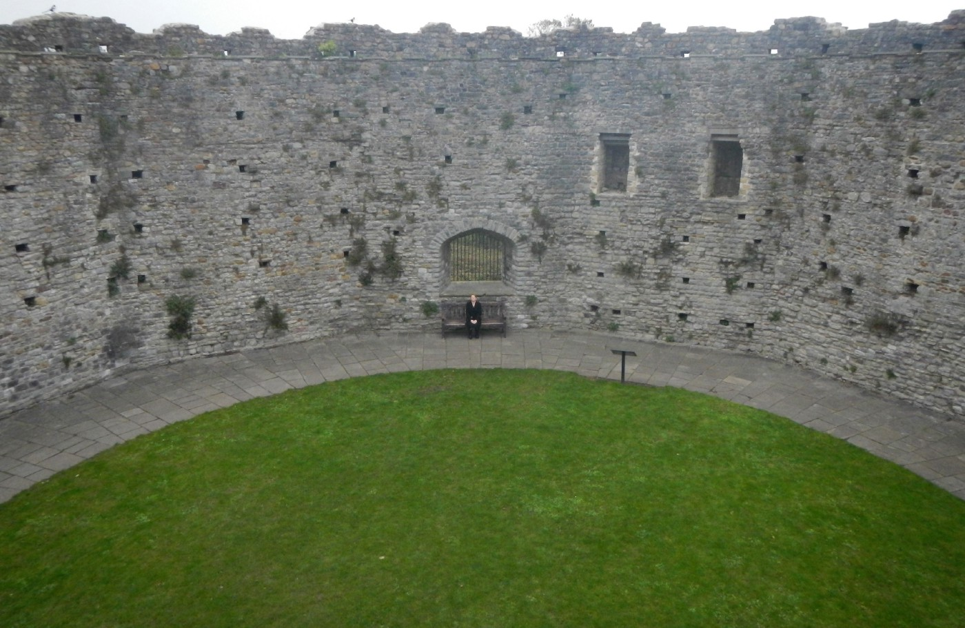 Woman sitting alone on a bench with castle walls in the background
