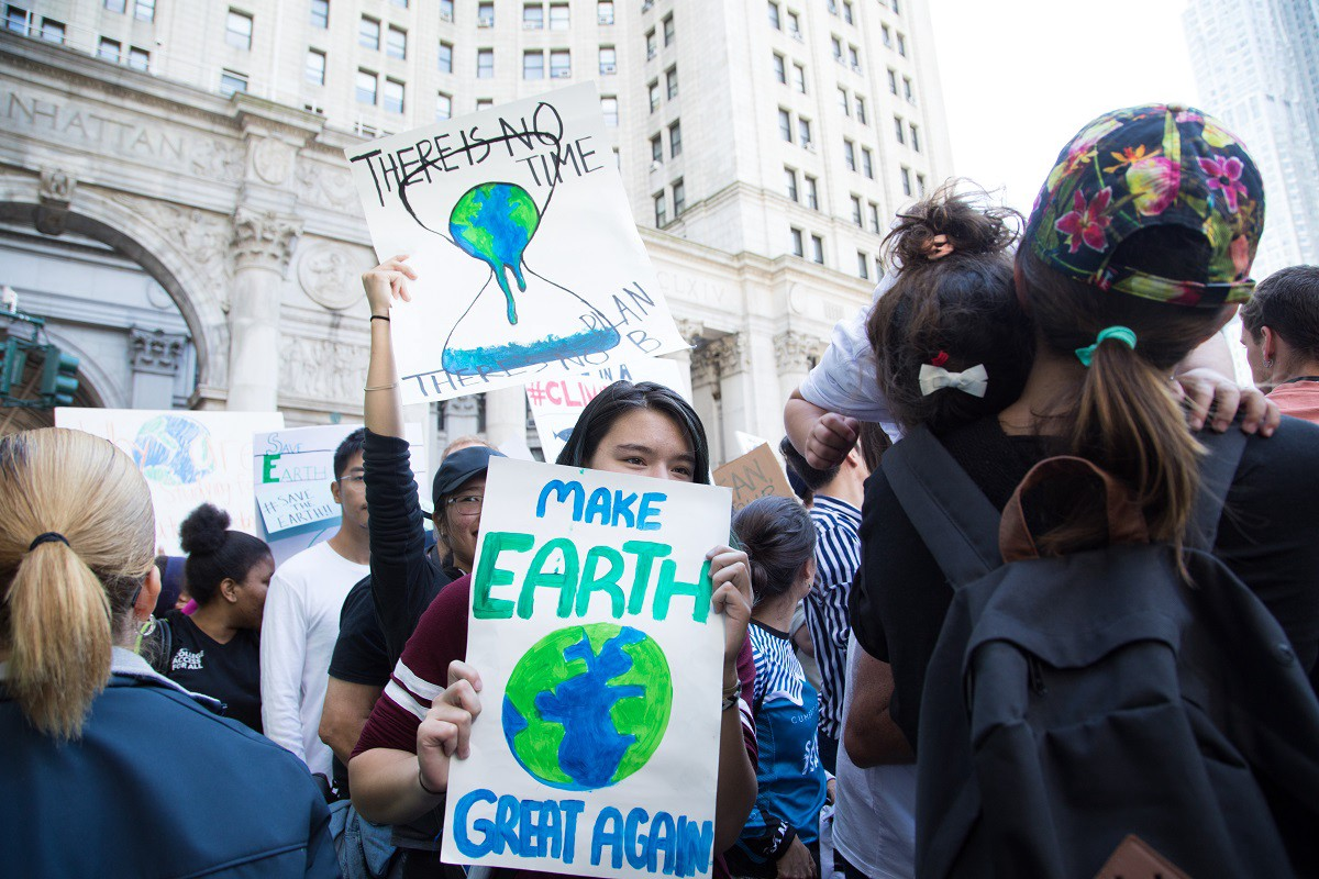 "At a climate protest, a girl holds up a sign that reads, ""Make Earth Great Again."""