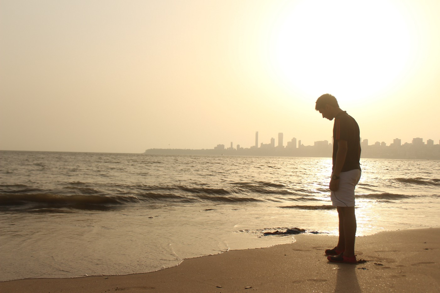 A software developer standing on the sea shore during sunset
