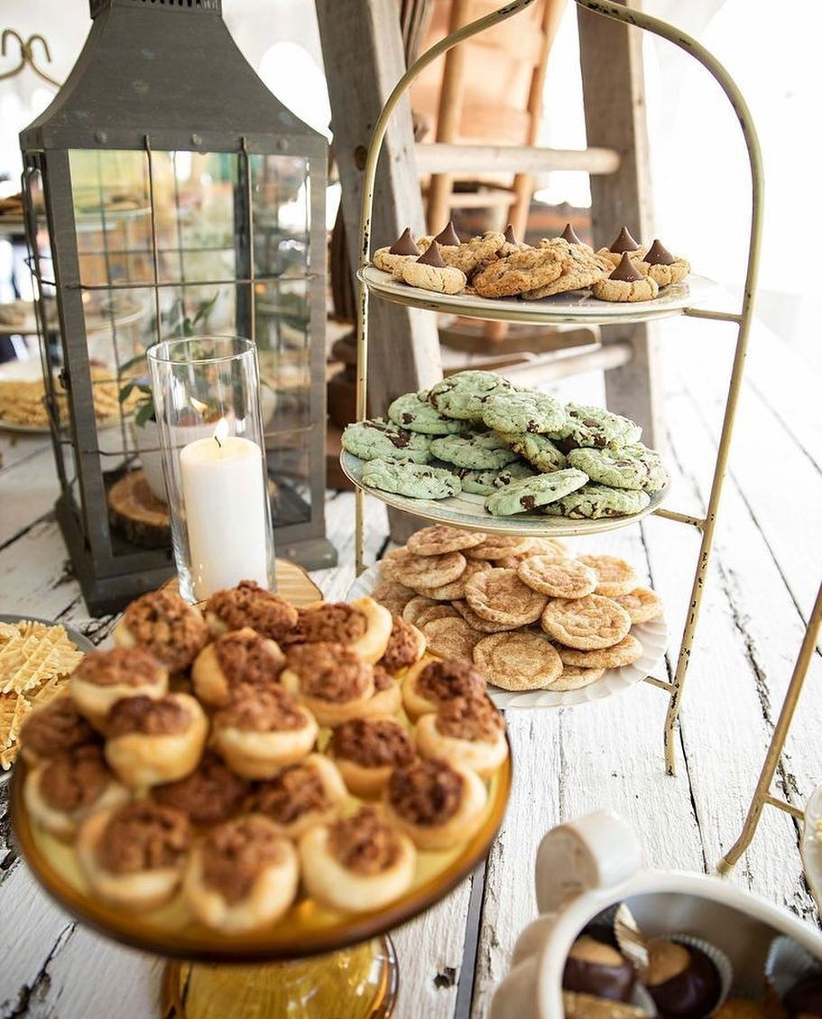 A variety of cookies on a multitiered serving rack next to a candle on a buffet table.