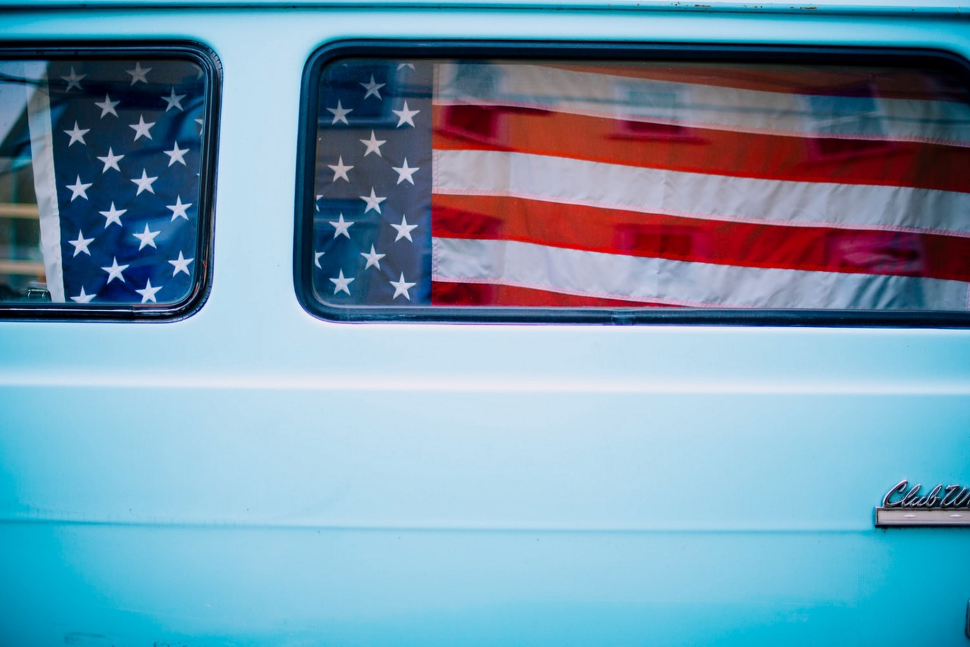 Photo of an American flag seen through a van window