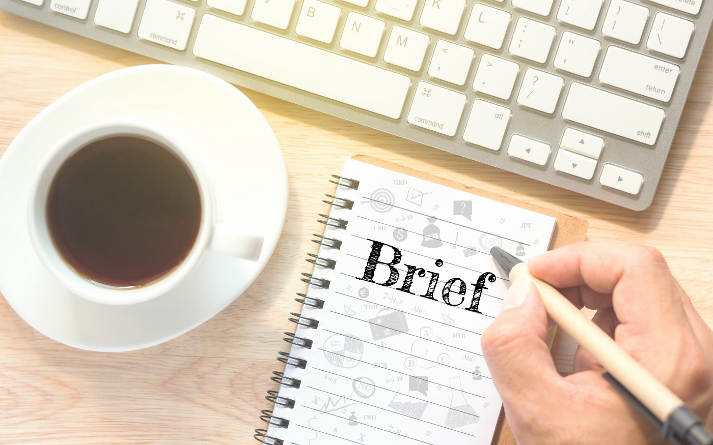"Picture of s hand writing ""Brief"" on a notepad next to a keyboard and mug of coffee"