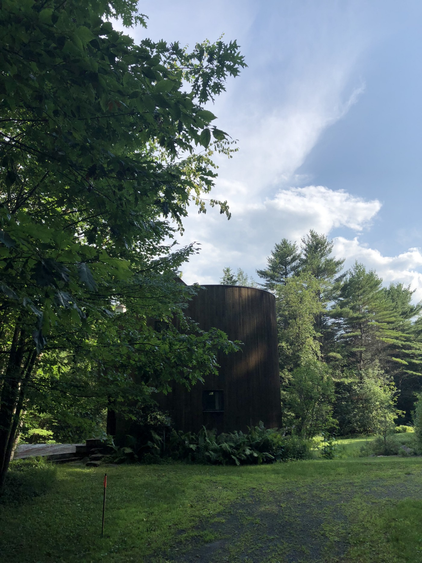 Surrounded by trees, a dark wooden cylinder of a house rising three stories out of the ground.