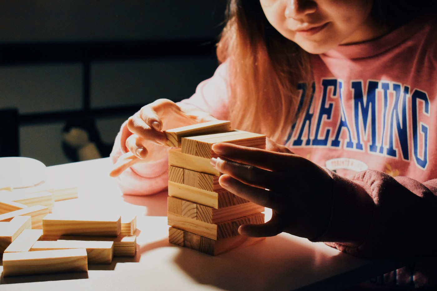 """A child in a pink jumper that reads """"dreaming"""" stacks wooden blocks on top of each other on a white desk."""