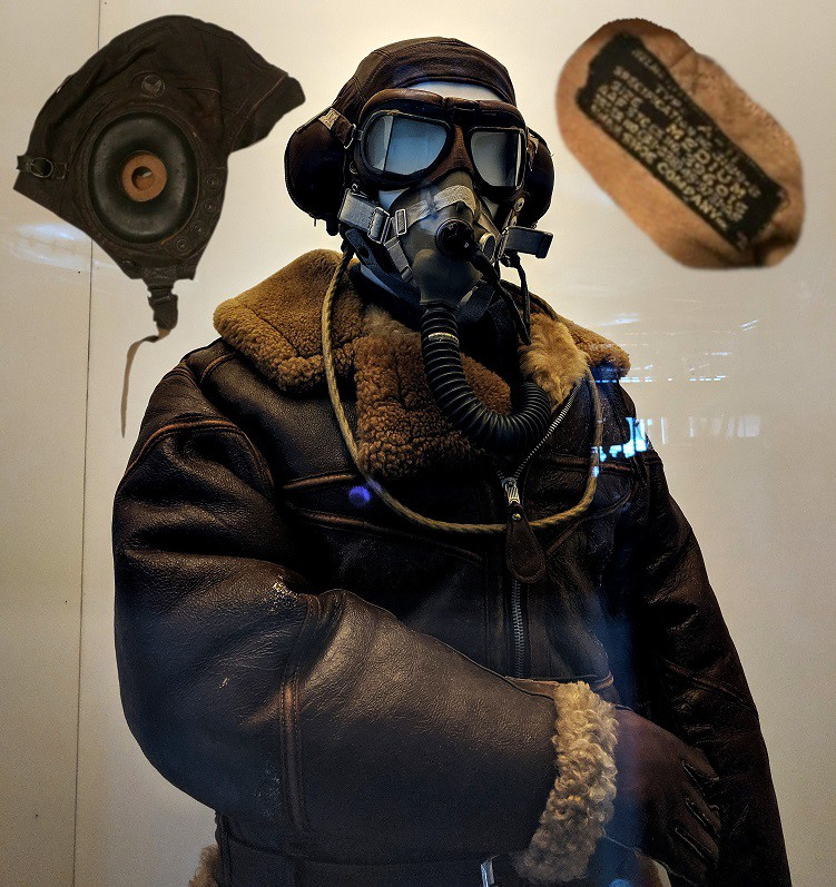 A manequin wearing all leather and a gas mask and photos of an old aviator helmet