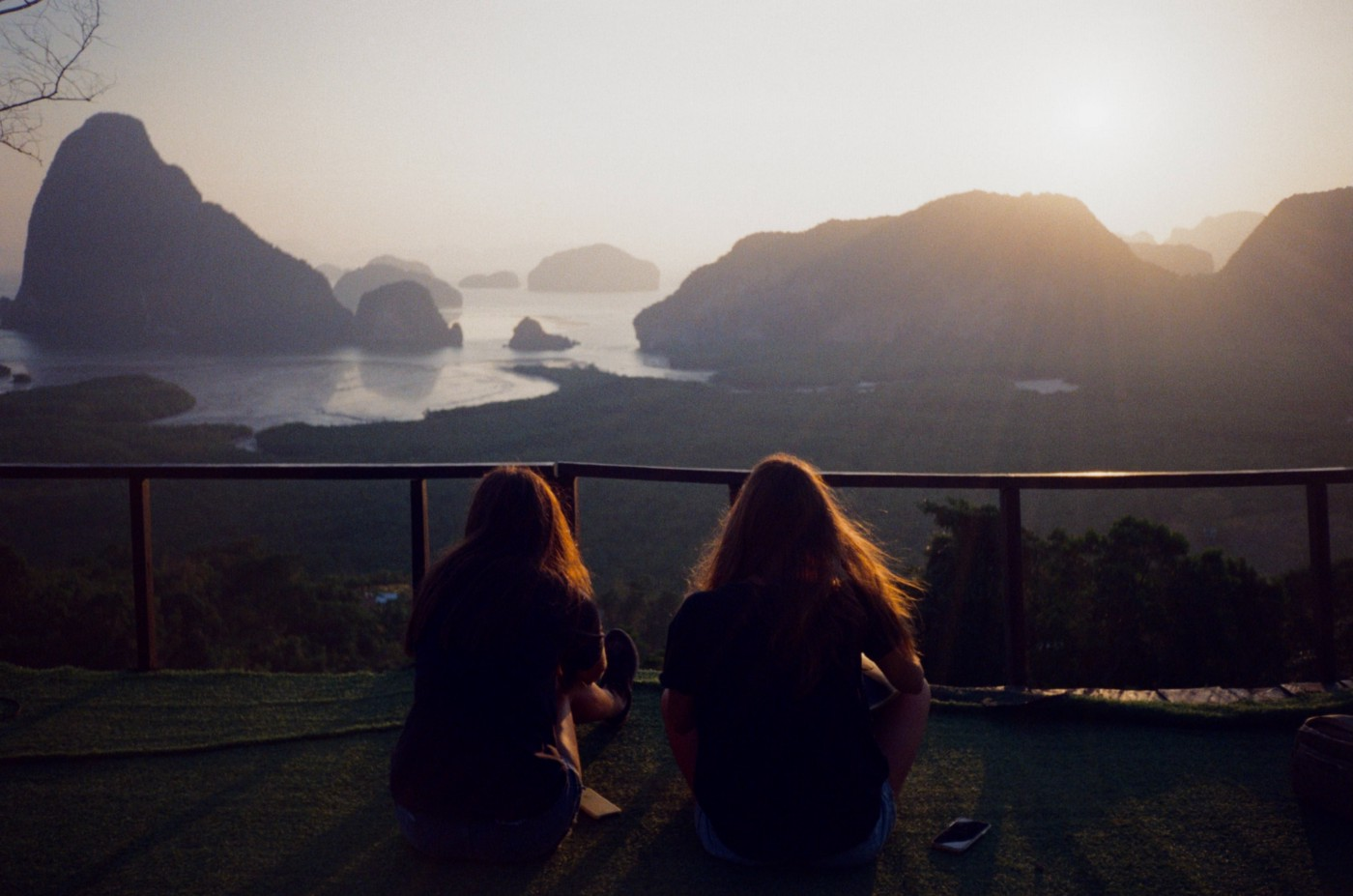 Two girls on a cliff look out toward the ocean sunset.