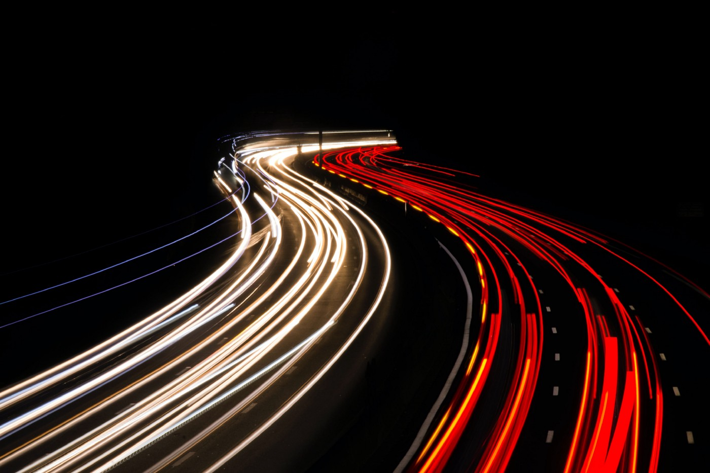 Headlights and taillights on a freeway, blurred into curving lines by long-exposure photography.