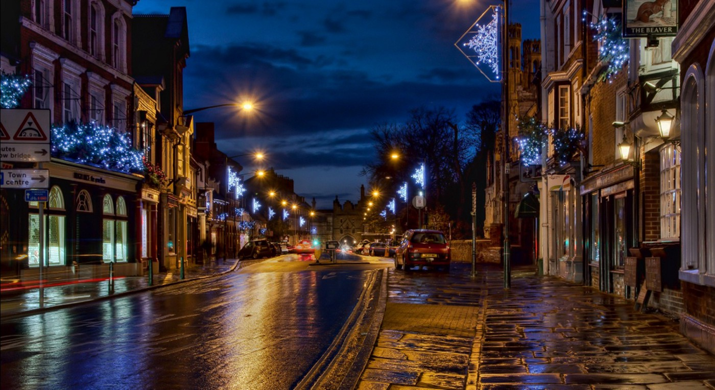 Image of a night time street scene in an English town where the road and paths are damp from evening rain and capture the reflections of street lights