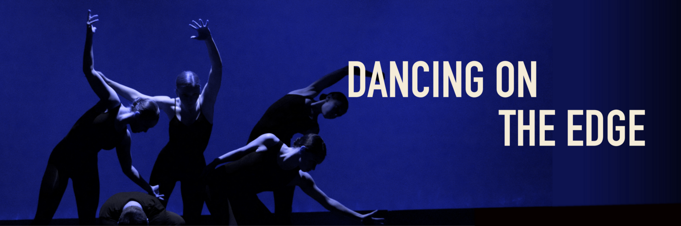 Dancers in low lighting, wearing black unitards, reach in different directions and intertwine their bodies.