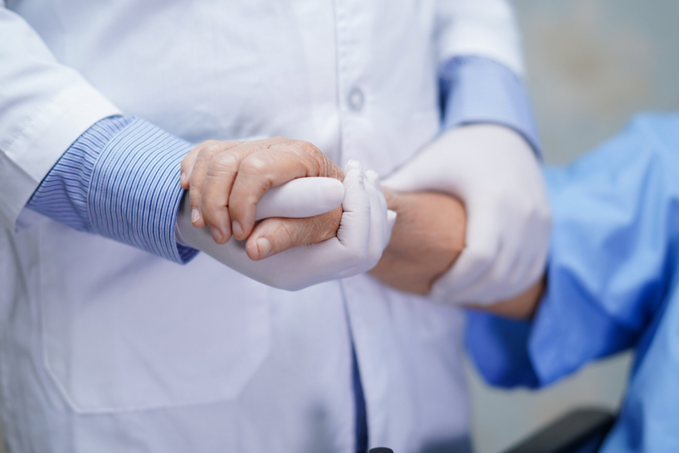 A photo of a patient holding a nurse's gloved hand.