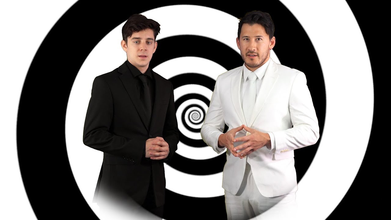 Thumbnail for the Unus Anus announcement video, featuring Ethan Nestor (left) and Mark Fischbach (right) standing in front of a black and white spiral.