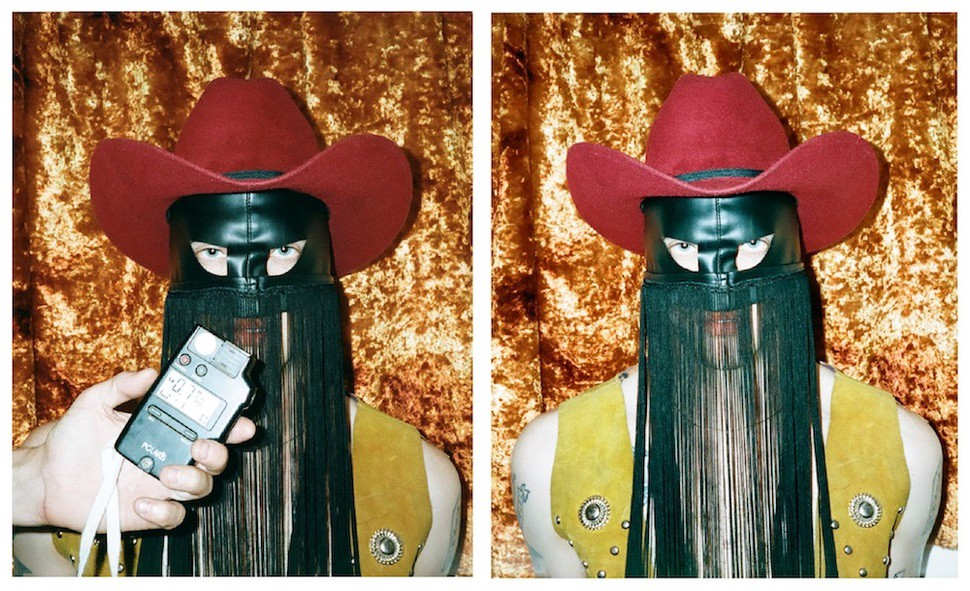 Orville Peck wears a red felt cowboy hat and a yellow vest. His signature leather fringe mask hangs on his face.